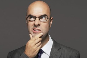 Bald businessman wearing glasses with hand on chin making funny face against gray background